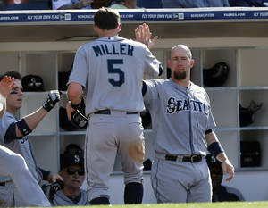 Photo - Seattle Mariners' Brad Miller is greeted by John Buck, right, and other teammates after scoring on a single by Robinson Cano in the fifth inning of a baseball game against the San Diego Padres Thursday, June 19, 2014, in San Diego. (AP Photo/Lenny Ignelzi)