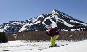 photo - This April 7, 2012  photo provided by Crested Butte Mountain Resort shows a youngster skiing with Crested Butte Mountain in the background. The Resorts new master development plan includes visions of one day adding about 440 acres, plus two new lifts. The plan includes adding 440 acres in the Teo Park and Drainage area, plus two lifts, a warming hut and ski patrol station in that area. Its intended to let intermediate skiers and riders take a chairlift to get to runs with more of a remote, backcountry feel than whats available on the front side of the mountain, without having to take an expert black diamond trail. (AP Photo/Crested Butte Mountain Resort, Nathan Bilow)