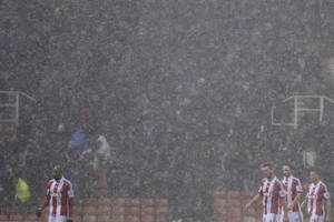 Photo - Stoke players walk from the pitch as hail falls during their team's English League Cup quarter-final soccer match against against Manchester United at the Britannia Stadium, Stoke, England, Wednesday Dec. 18, 2013. (AP Photo/Jon Super)