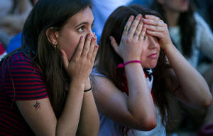 Photo - Allison DiFilippo, left, and Samantha Donat, both of New York, react to a last-minute goal that put Portugal even with United States at the end of their 2014 World Cup Group G soccer match, while watching a large screen broadcast on Governor's Island in New York, Sunday, June 22, 2014. (AP Photo/Craig Ruttle)
