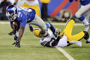 Photo -   New York Giants' David Wilson (22) is tackled by Green Bay Packers' Jarrett Bush during the first half of an NFL football game, Sunday, Nov. 25, 2012, in East Rutherford, N.J. (AP Photo/Bill Kostroun)