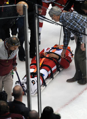 Photo - Detroit Red Wings defenseman Niklas Kronwall, of Sweden, is taken off the ice on a stretcher after being checked against the boards in the first period of an NHL hockey game against the Colorado Avalanche on Thursday, Oct. 17, 2013, in Denver. (AP Photo/Chris Schneider)