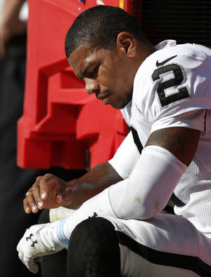 Photo - Oakland Raiders quarterback Terrelle Pryor (2) looks at his injured thumb while on the bench during the second half of an NFL football game against the Kansas City Chiefs at Arrowhead Stadium in Kansas City, Mo., Sunday, Oct. 13, 2013. The Chiefs defeated the Raiders 24-7. (AP Photo/Ed Zurga)