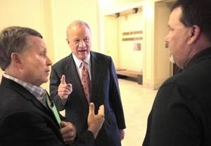 Photo - Barry Switzer, center, talks with Ernest Clark, a concerned citizen, left, and Kim Longest with the OFBCA (Oklahoma Football Coaches Association), right, at the state Capitol during the hearing on OSSAA and high school sports, Tuesday, September 17, 2013. Longest testified during the hearing. Photo by David McDaniel,