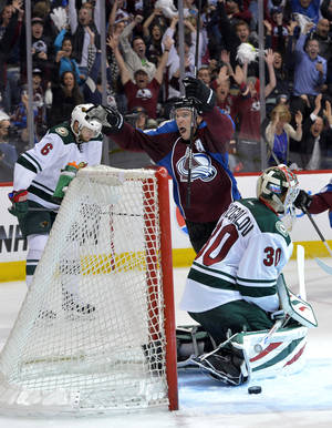 Photo - Colorado Avalanche center Paul Stastny (26) celebrates scoring the game winning goal against Minnesota Wild goalie Ilya Bryzgalov (30) from Russia as Marco Scandella (6) reacts during the fourth period in Game 1 of an NHL hockey first-round playoff series on Thursday, April 17, 2014, in Denver. Colorado beat Minnesota 5-4 in overtime.  (AP Photo/Jack Dempsey)