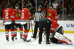 Photo - Chicago Blackhawks goalie Corey Crawford, right, is tended to after suffering an injury during the first period of an NHL hockey game against the Florida Panthers on Sunday, Dec. 8, 2013, in Chicago, Ill. (AP Photo/Andrew A. Nelles)