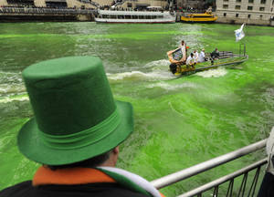 Photo - A spectator looks on as the Chicago River is dyed green ahead of the St. Patrick's Day parade in Chicago, Saturday, March, 16, 2013. With the holiday itself falling on a Sunday, many celebrations were scheduled  for Saturday because of religious observances. (AP Photo/Paul Beaty)