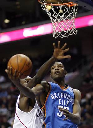 Photo - Philadelphia 76ers center Samuel Dalembert, left, reaches to block the shot of Oklahoma City Thunder guard Kevin Durant, right, during the first half of an NBA basketball game Saturday, Nov.15, 2008, in Philadelphia. (AP Photo/Tom Mihalek) ORG XMIT: PATM102