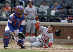 Photo - While New York Mets catcher Travis d'Arnaud, left, waits for the ball, Washington Nationals' Bryce Harper slides safely home during the seventh inning of the baseball game at Citi Field, Thursday, April 3, 2014 in New York. (AP Photo/Seth Wenig)