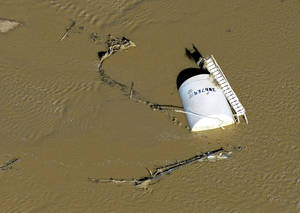 Photo - File - In this Sept. 17, 2013, file photo, a crude oil storage tank lies on its side in flood water along the South Platte River in Weld County, Colo. Denver-based Zavanna LLC oil company probably will be sanctioned for not heeding a warning to properly secure a North Dakota well that was swamped by floodwaters and spilled oil near the confluence of the Yellowstone and Missouri rivers, a state health official said Monday, March 17, 2014. (AP Photo/John Wark, File)