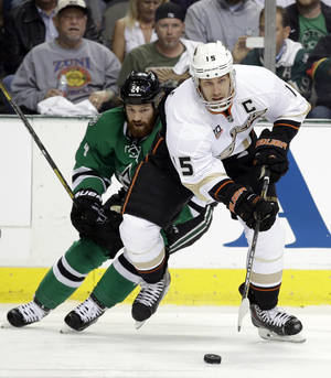 Photo - Anaheim Ducks' Ryan Getzlaf (15) controls the puck as he moves away from Dallas Stars' Jordie Benn (24) in the first period of Game 3 of a first-round NHL hockey Stanley Cup playoff series game, Monday, April 21, 2014, in Dallas. (AP Photo/Tony Gutierrez)