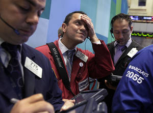 Photo -   Trader Michael Zicchinolfi, center, works on the floor of the New York Stock Exchange Monday, Oct. 22, 2012. A weak forecast from heavy equipment maker Caterpillar and other poor earnings results weighed on the U.S. stock market in early trading. (AP Photo/Richard Drew)