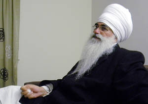 Photo - In this March 2012 photo provided by his family, Punjab Singh poses at a Sikh temple in Glen Rock, N.J. Singh was critically injured in a shooting rampage at a Sikh temple in Oak Creek, Wis., in August 2012 that left six people dead. The 65-year-old Sikh priest had remained largely unresponsive at a Wisconsin care facility until January 2013 when he began showing signs of cognitive improvement. (AP Photo/Family photo)