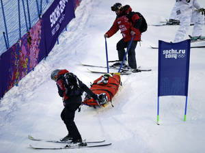 Photo - United States' Heidi Kloser is stretchered off the course after crashing in a warm up run before qualifying in the women's moguls at the Rosa Kutor Exreme Park ahead of the 2014 Winter Olympics, Thursday, Feb. 6, 2014, in Krasnaya Polyana, Russia. (AP Photo/Andy Wong)