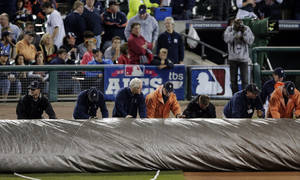 Photo -   Grounds crew roll out a tarp after Game 4 of the American League championship series between the Detroit Tigers and the New York Yankees was postponed due to rain Wednesday, Oct. 17, 2012, in Detroit. (AP Photo/Charlie Riedel)