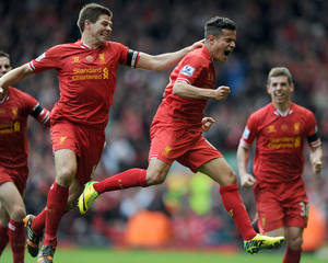 Photo - Liverpool's Philippe Coutinho right, celebrates with team-mate Steven Gerrard left, after he scores the third goal of the game for his side during their English Premier League soccer match against Manchester City at Anfield in Liverpool, England, Sunday April. 13, 2014. (AP Photo/Clint Hughes)