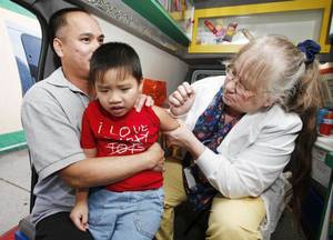 Photo -  Trieu Bui holds his son Jason as Diane Johnson gives him a shot inside an Oklahoma Caring Van. Photo by Steve Gooch, The Oklahoman Archives   <strong>Steve Gooch -   </strong>