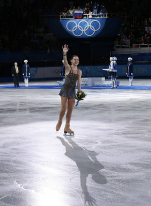 Photo - Adelina Sotnikova of Russia waves to spectators after placing first in the results area after completing her routine in the women's free skate figure skating finals at the Iceberg Skating Palace during the 2014 Winter Olympics, Thursday, Feb. 20, 2014, in Sochi, Russia. (AP Photo/Bernat Armangue)