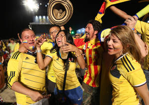 Photo - Colombia soccer fans celebrate the third goal scored by their team as they watch a live telecast of their team's World Cup match with Japan inside the FIFA Fan Fest area on Copacabana beach, in Rio de Janeiro, Brazil, Tuesday, June 24, 2014. Substitute James Rodriguez scored a brilliant goal and set up two more for Jackson Martinez as Colombia beat Japan 4-1 on Tuesday to confirm top spot in Group C and eliminate the Asian champions from the World Cup. (AP Photo/Leo Correa)