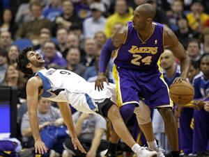 photo - Minnesota Timberwolves&#039; Ricky Rubio left, of Spain, falls to the floor after a called charge on Los Angeles Lakers&#039; Kobe Bryant in the first quarter of an NBA basketball game Friday, Feb. 1, 2013, in Minneapolis. (AP Photo/Jim Mone)