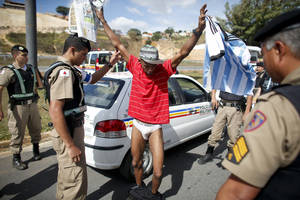 Photo - Holding an Argentine soccer jersey, Denis Andre Oliveira, 33, of Brazil, is searched by police after he was detained for entering the Cidade do Galo sports complex where Argentina's soccer team trains in Vespasiano, near Belo Horizonte, Brazil, Wednesday, June 18, 2014. Oliveira said he wanted to get an autograph of Argentina's Lionel Messi. On June 11, Oliveira broke into Independencia Stadium where Argentina was training shined Messi's cleats. (AP Photo/Victor R. Caivano)