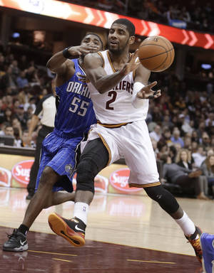 Photo - Cleveland Cavaliers' Kyrie Irving (2) passes the ball in front of Orlando Magic's E'Twaun Moore (55) during the second quarter of an NBA basketball game Wednesday, Feb. 19, 2014, in Cleveland. (AP Photo/Tony Dejak)