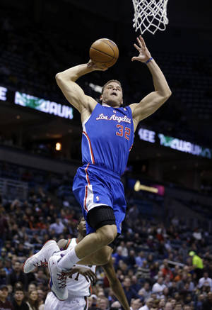Photo - Los Angeles Clippers (32) Blake Griffin dunks against Milwaukee Bucks' Brandon Knight, back, during the first half of an NBA basketball game, Monday, Jan. 27, 2014, in Milwaukee. (AP Photo/Jeffrey Phelps)