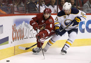 Photo - Phoenix Coyotes' David Schlemko (6) and Buffalo Sabres' Cody Hodgson (19) skate after the puck during the first period of an NHL hockey game on Thursday, Jan. 30, 2014, in Glendale, Ariz. (AP Photo)