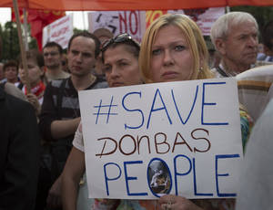 "Photo - A woman holds a poster reading  ""Save Donbas People"" as Russian Communists party activists gather in support of pro-Russian fighters and local citizens who live in Donetsk and Luhansk regions of eastern Ukraine in Moscow, Russia, Thursday, July 3, 2014. Ukraine's president shook up the leadership of his struggling military on Thursday, appointing a new defense minister and top general tasked with stamping out the corruption that has left the country's armed forces faltering before a pro-Russian insurgency.  (AP Photo/Alexander Zemlianichenko)"