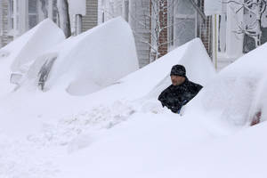 Photo - John Silver shovels snow between buried cars in front of his home on Third Street in South Boston, Saturday, Feb. 9, 2013. (AP Photo/Gene J. Puskar)