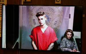Photo - Justin Bieber appears in court via video feed, Thursday, Jan. 23, 2014, in Miami. Bieber was released from jail Thursday following his arrest on charges of driving under the influence, driving with an expired license and resisting arrest. Police say they stopped the 19-year-old pop star while he was drag-racing down a Miami Beach street before dawn. (AP Photo/The Miami Herald, Walter Michot, Pool)