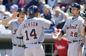 Photo - Detroit Tigers' Austin Jackson, center, celebrates with teammates Andy Dirks, left, and Jordan Lennerton, right, after the three players scored on a double by teammate Nick Castellanos during the first inning of an exhibition baseball game against the Detroit Tigers Friday, Feb. 28, 2014, in Clearwater, Fla. (AP Photo/Charlie Neibergall)