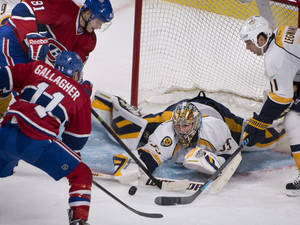 Photo - Montreal Canadiens' Brendan Gallagher tries to put the puck past Nashville Predators goalie Pekka Rinne during the second period of an NHL hockey game, Saturday, Oct. 19, 2013 in Montreal. (AP Photo/The Canadian Press, Peter McCabe)