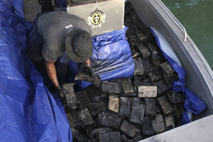 Photo - In this undated photo provided by the Australian Federal Police, an officer gathers packages of cocaine found on a yacht in Port Vila, Vanuatu. The 750 kilograms (1,650 pounds) of cocaine worth 370 million Australian dollars ($330 million) were found and seized on Monday, Aug. 19, 2013 after the U.S. Drug Enforcement Administration and Australian Federal Police collaborated with South Pacific governments, officials said Friday, Aug. 23, 2013. (AP Photo/Australian Federal Police) EDITORIAL USE ONLY