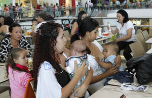 photo - Costa Rican women breast feed their babies during a pro-breastfeeding demonstration at the Plaza Lincoln shopping center in San Jose, Costa Rica, Saturday, Jan. 12, 2013. At least 50 mothers gathered in the mall's fast food area and breastfed infants for nearly two hours Saturday, protesting over the shopping center forcing a woman to stop nursing her daughter a week earlier.  (AP Photo/Enrique Martinez)