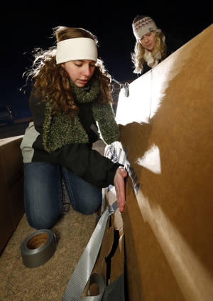 Photo - Macy Bratcher, 13, left, and Meagan Johnson, 23, set up their cardboard shelter.