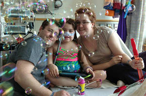 Photo - FILE - In this May 30, 2013 file photo provided by the Murnaghan family, Sarah Murnaghan, center, celebrates the 100th day of her stay in Children's Hospital of Philadelphia with her father, Fran, left, and mother, Janet. The 10-year-old suburban Philadelphia girl received a lung transplant there Wednesday, June 12, 2013, her family said. (AP Photo/Murnaghan Family, File)
