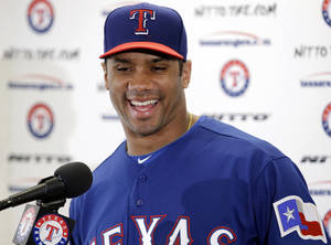 Photo - Seattle Seahawks quarterback Russell Wilson responds to a question during a news conference after a full day's workout with the Texas Rangers during spring training baseball practice, Monday, March 3, 2014, in Surprise, Ariz. (AP Photo/Tony Gutierrez)