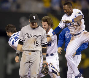 photo -   Chicago White Sox second baseman Gordon Beckham (15) walks off the field while Kansas City Royals' Eric Hosmer (35), Mike Moustakas (8) and Jarrod Dyson (1) celebrate during the ninth inning of a baseball game at Kauffman Stadium in Kansas City, Mo., Thursday, Sept. 20, 2012. Hosmer singled and Dyson scored the winning run as the Royals defeated the White Sox 4-3. (AP Photo/Orlin Wagner)