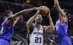 Photo - San Antonio Spurs' Tim Duncan (21) is pressured by 76ers' Thaddeus Young, left, and Hollis Thompson, right, during the first half of an NBA basketball game, Monday, March 24, 2014, in San Antonio. (AP Photo/Eric Gay)