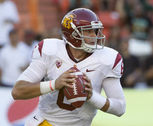 Photo - Southern California quarterback Cody Kessler (6) rolls out to pass while playing against Hawaii during the second quarter of an NCAA college football game Thursday, Aug. 29, 2013, in Honolulu. (AP Photo/Eugene Tanner)