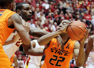 photo - Iowa State forward Anthony Booker tries to knock the ball away from Oklahoma State guard Markel Brown (22) during the first half of an NCAA college basketball game, Wednesday, March 6, 2013, in Ames, Iowa. (AP Photo/Justin Hayworth) ORG XMIT: IAJH103