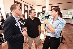 Photo - Stephen Koranda, executive director of the Norman Convention and Visitors Bureau, left, visits with resident Matt Lamey and Jen Tregarthen, also with the bureau, at the unveiling of the bureau's new logo at the Santa Fe Depot. OKLAHOMAN ARCHIVE PHOTO