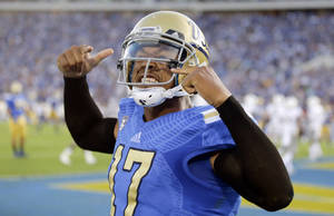 Photo - UCLA quarterback Brett Hundley celebrates a touchdown against Nevada during the first half of an NCAA college football game in Pasadena, Calif., Saturday, Aug. 31, 2013. (AP Photo/Chris Carlson)