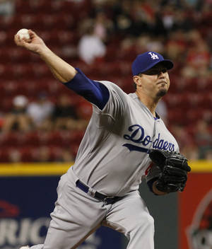 Photo - Los Angeles Dodger Josh Beckett pitches in the first inning of the baseball game between the Los Angeles Dodgers and the Cincinnati Reds in Cincinnati Tuesday June 10, 2014. (AP Photo/Tom Uhlman)