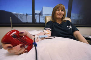 Photo - Top: Debi Croft donates blood.  Photos By David McDaniel, The Oklahoman