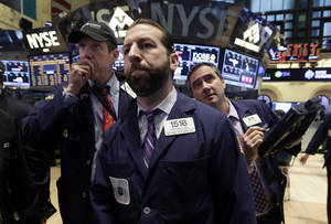 Photo -  Greg Mulligan, center, works with fellow traders Wednesday on the floor of the New York Stock Exchange. The U.S. stock market is edging lower in early trading after a modest recovery the day before. AP Photo  <strong>Richard Drew -  AP </strong>