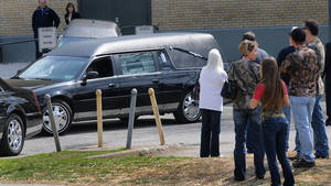"Photo - A hearse leaves the Municipal Auditorium in Charleston, W.Va. after a joint funeral for ""Buckwild"" star Shain Gandee and his uncle David Gandee Sunday afternoon, April 7, 2013. Gandee, his 48-year-old uncle, David Gandee, and 27-year-old friend Donald Robert Myers were found dead April 1 in a sport utility vehicle that was partially submerged in a deep mud pit near Sissonville. (AP Photo/The Charleston Gazette, Kenny Kemp)"