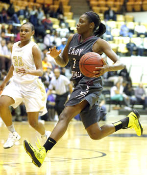 photo - Northeast Lanesia Williams drives to the basket during the girl's basketball game between Northeast and Midwest City at the Midwest City/Del City Holiday Invitational,  Saturday,Dec. 29, 2012. Photo by Sarah Phipps, The Oklahoman