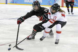 Photo - Marie-Philip Poulin of Canada and Jessica Lutz of Switzerland battle for control of the puck during the second period of the women's ice hockey game at the Shayba Arena during the 2014 Winter Olympics, Saturday, Feb. 8, 2014, in Sochi, Russia. (AP Photo/Matt Slocum)